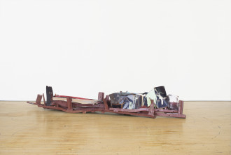 A long, low-lying sculpture made of red, dark blue, and green metal parts rests on a wooden floor.