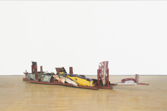 A long, low-lying sculpture made of red, white, yellow, and multicolored metal parts rests on a wooden floor.