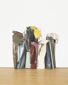 A vertically oriented sculpture with three standing sections made of multicolored metal parts rests on a wooden floor.