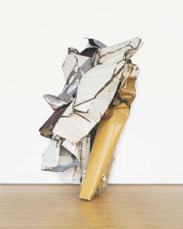 A crumpled-and-folded, white-and-yellow, metallic object rests on a wooden floor in front of a white background.