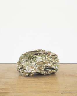 A crumpled ball-like sculpture made from reflective silvery green metal parts rests on a wooden floor.