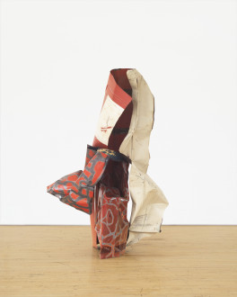 A vertically oriented sculpture made of red, white, and silver-striped red metal parts rests on a wooden floor.