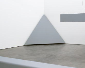 A large, gray, equilateral triangle is placed in a corner.