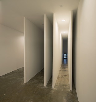 Two television monitors display camera output at the far end of one of five narrow, hallway-like spaces of varying width, formed by thin white walls.