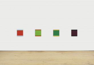 Four multicolored squares hang in a row on a white wall.