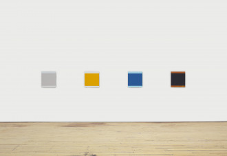 Four multicolored squares hang n a row on a white wall.