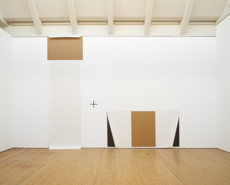A vertically oriented, rectangular, white-and-brown work on paper is placed near the ceiling and stretches along a white wall down to a wooden floor. Next to it is a horizontally oriented, rectangular, white, brown, and black work on paper that is placed on the wall just above the floor. A plus sign is placed on the wall between the two works on paper.