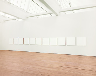 Room with eleven evenly spaced, white squares placed along a horizontal white wall above a wooden floor.