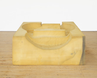 A foam square with curved forms carved into its top rests on a wooden floor in front of a white background.