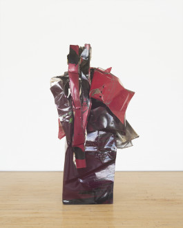 A columnar sculpture made of red metal parts that twist together rests on a wooden floor.