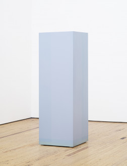 A tall, light blue column with two slightly darker stripes toward its bottom is centered on a wooden floor in front of two white walls.