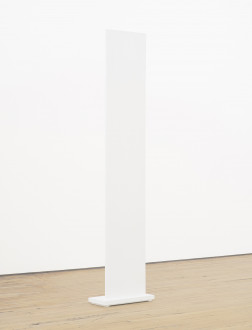 A vertically oriented, white panel with a small rectangular base is placed on a wooden floor in front of a white wall.