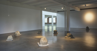 Seven large rocks rest on beige pillows and are arranged in a loose circle on a concrete floor with a single lightbulb hanging above and a spotlight to the right.