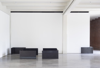 Four steel plates bent at 90-degree angles sit on the floor in an open rectangular configuration near two more plates that are situated by gallery corners.