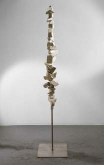 Balanced on a bronze pole and attached to a flat base is a thin vertical sculpture made of several wooden blocks of varying sizes that are stacked on top of one another.