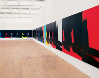 Twenty-five canvases hang edge to edge and low to the floor along a wall and in the corner of a gallery. Each painting features an identical abstract mark painted in black, gray, red, green, yellow, pink, purple, or blue.