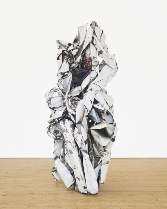 A vertically oriented sculpture made of white metal parts that are twisted around an iridescent metal center rests on a wooden floor.