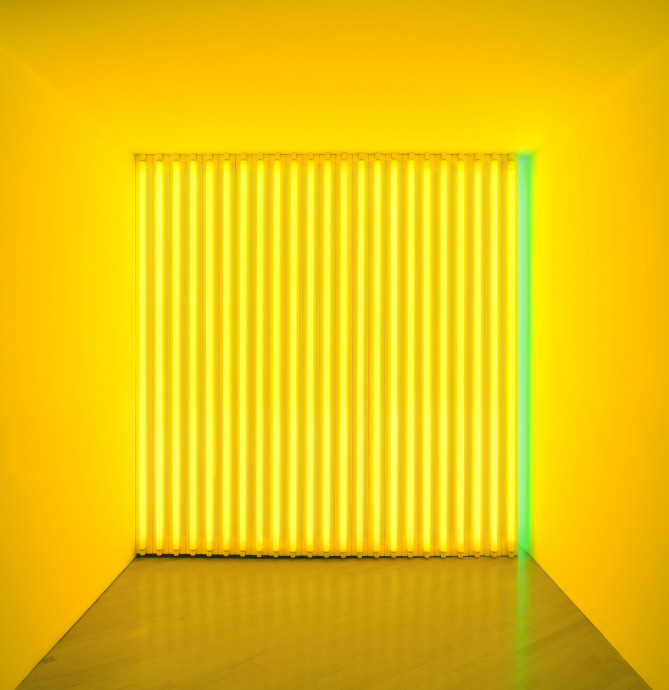 A square space is barricaded by several vertical yellow fluorescent tubes and one green tube on the right.