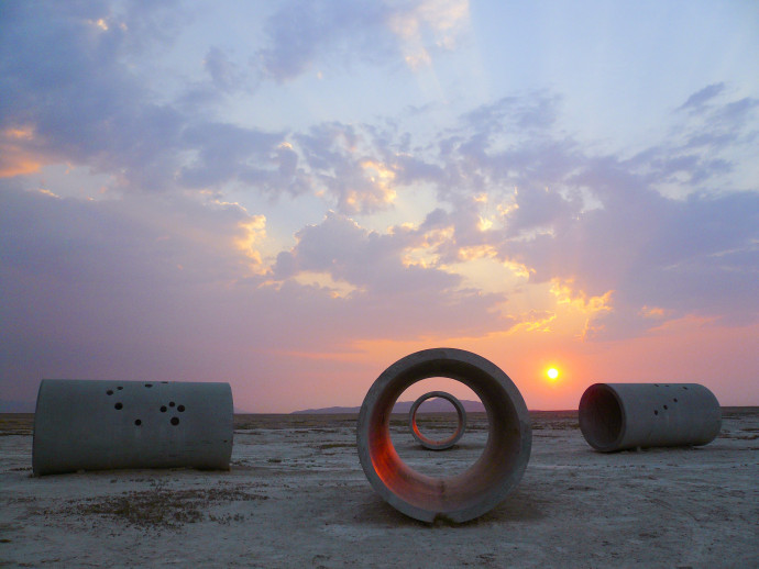 Four large concrete cylinders lie on their sides in the desert. The sun is casting a pink glow along the horizon of an otherwise blue sky.