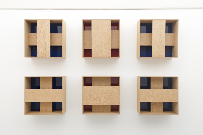 6 wooden boxes, each has 2 strips of wood forming a cross over a red or blue interior.