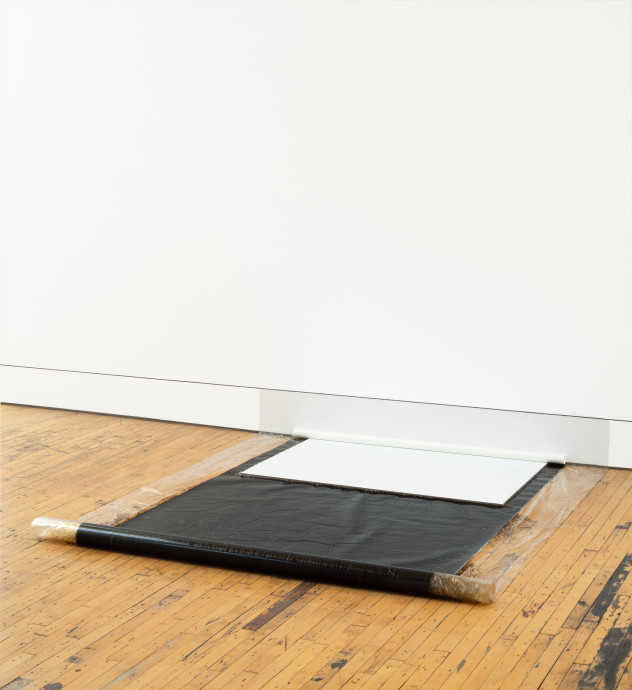 A roll of a rectangular-shaped, slightly transparent, and mostly black object extends from a white wall and rests on a wooden floor. A smaller, white, rectangular object also touches the wall and is placed above the black unrolled object.